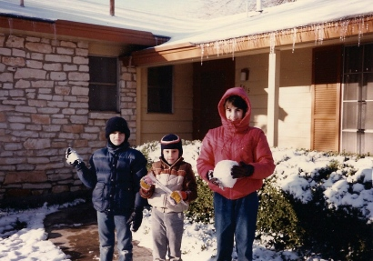 My children make snowballs and show off icicles before the snow melts.